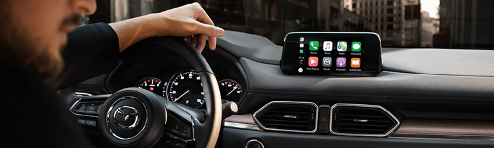 driver in the 2019 Mazda CX-5 using the Apple CarPlay