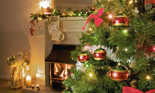 A decorated Christmas tree at home in front of a fireplace