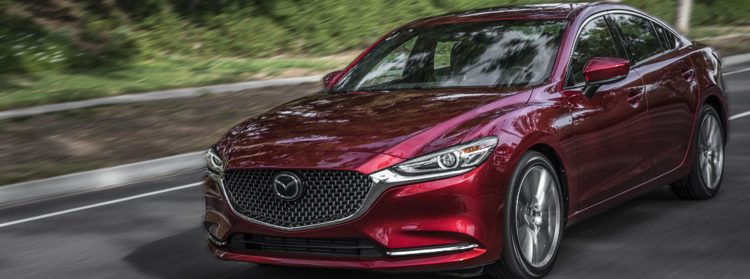 2018 Mazda6 red coat paint finish driving down road next to green forest hill