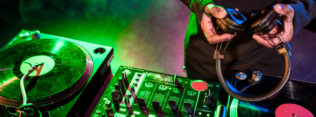 Dj holding headphones over mixing record board in a club with nightlife lighting and music