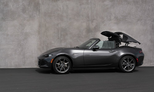 2018 Mazda MX-5 Miata RF hard top exterior shot parked next to a wall as hard top convertible process is retracting or extending