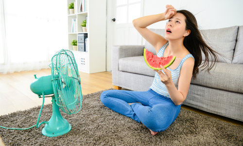 a woman eating watermelon in front of a fan to stay cool in the summer heat