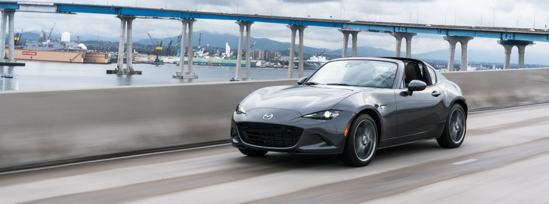 2019 Mazda MX-5 Miata exterior shot gray paint job driving on a highway near a bridge over the water