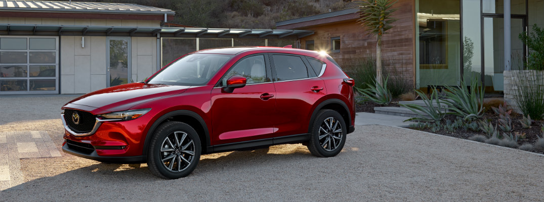 2019 Mazda CX-5 exterior shot with red paint color parked on a sand gravel driveway outside a desert vacation house