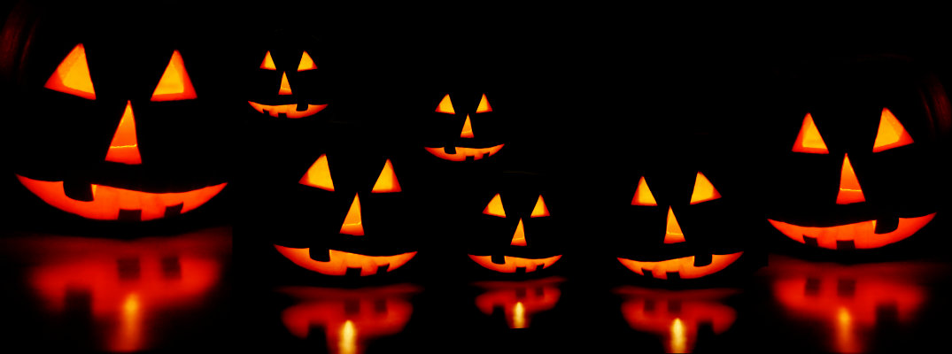 a row of carved and candle lit pumpkin jack o' lanterns in the dark