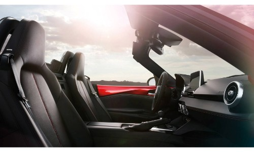 2018 Mazda MX-5 Miata interior side shot of front seating upholstery with soft top roof down and a sun glare
