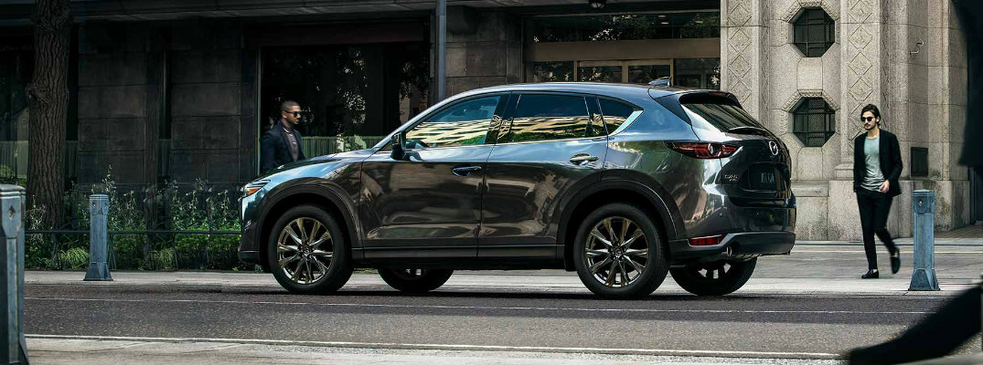 2019 Mazda CX-5 Signature trim exterior side shot with gray metallic paint color parked outside a stone building as pedestrians walk by