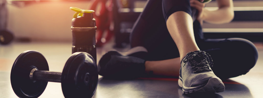 a woman in her gym outfit sitting down on the floor near a dumbbell curling weight and her water bottle