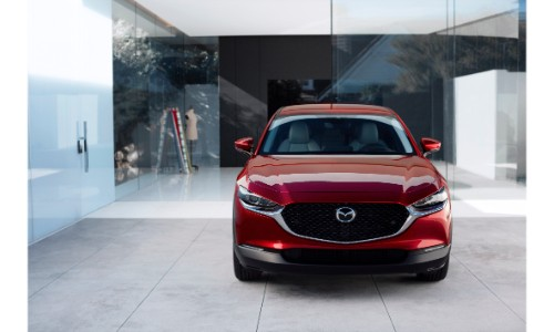 2020 Mazda CX-30 compact crossover SUV exterior front shot with soul red crystal paint color parked in front of glass panels