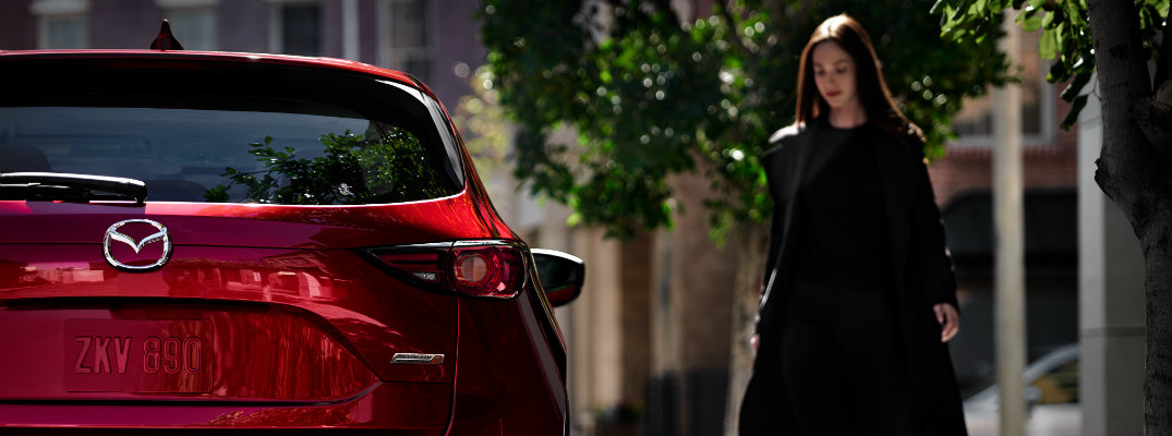 2019 Mazda CX-5 Signature trim with skyactiv diesel engine powertrain exterior rear shot with red paint color as a woman approaches