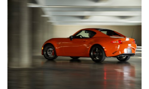 2019 Mazda MX-5 Miata 30th Anniversary Edition exterior side shot with racing orange paint color and a blurry background