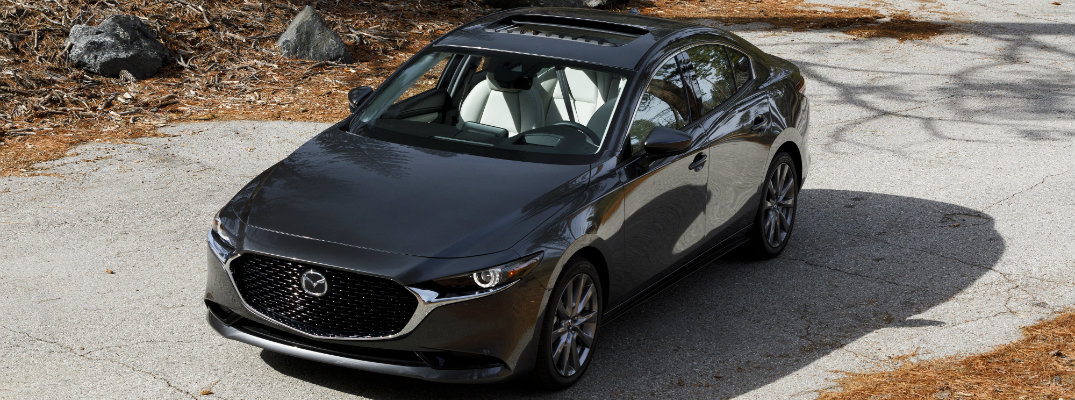 2019 Mazda3 exterior overhead shot with gray metallic paint color parked in a barren, fall and autumn forest