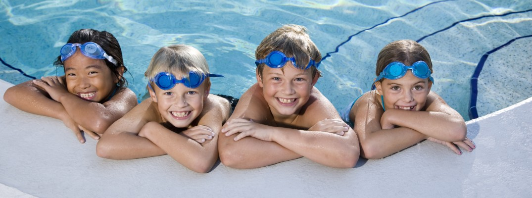 A row of children hanging onto the edge of the swimming pool with goggles on as they smile for a photo while in the water