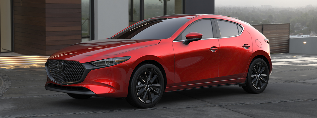 2020 Mazda3 Hatchback exterior shot with soul red crystal metallic paint color parked outside a luxury house with fog overlooking a city