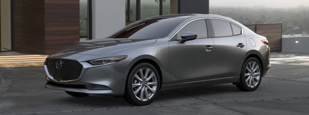 2020 Mazda3 Sedan exterior shot with machine gray metallic paint color parked outside a luxury house with fog overlooking a city