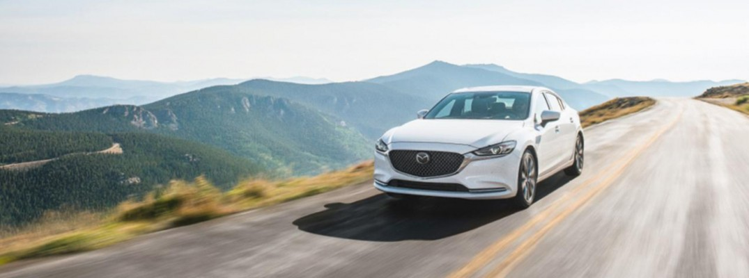 2020 Mazda6 sedan exterior shot with snowflake white pearl mica paint color driving down a country highway near grass mountains and a bright sky
