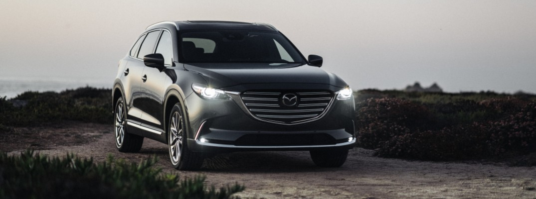 2020 Mazda CX-9 SUV exterior shot with LED headlights on parked on a dirt road near overgrown grass wilderness as the sky begins to darken at night