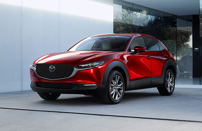 A red Mazda CX-30 parked near a building