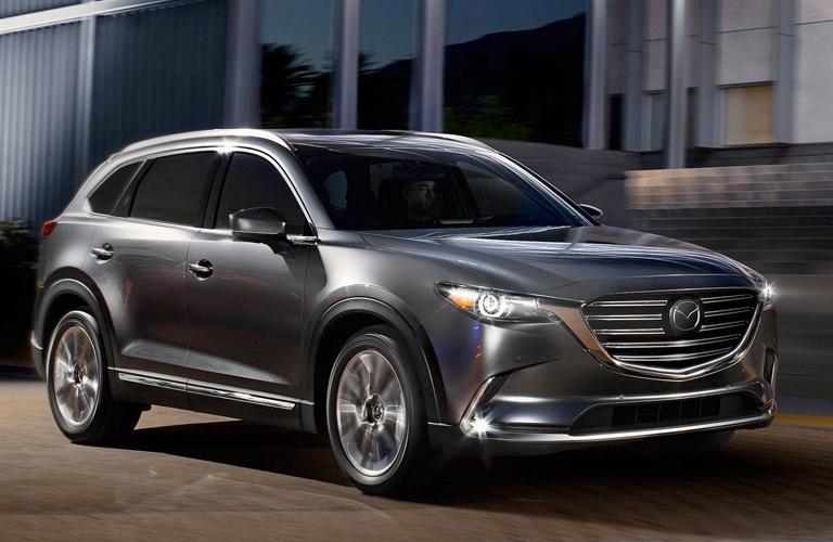 A gray 2019 Mazda CX-9 driving down a suburban road.