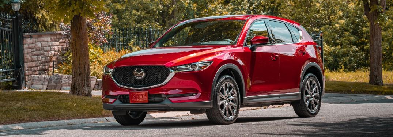 A red 2020 Mazda CX-5 Signature driving down a park area.