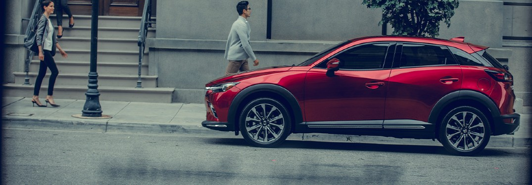 The side view of a red 2020 Mazda CX-3 parked in the rain.
