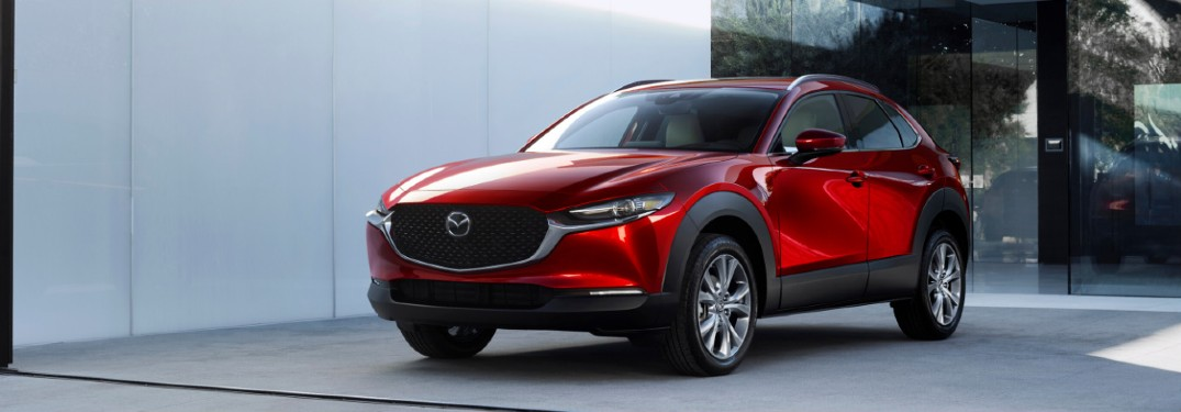 The front and side image of a red 2020 Mazda CX-30 parked near a concrete wall.