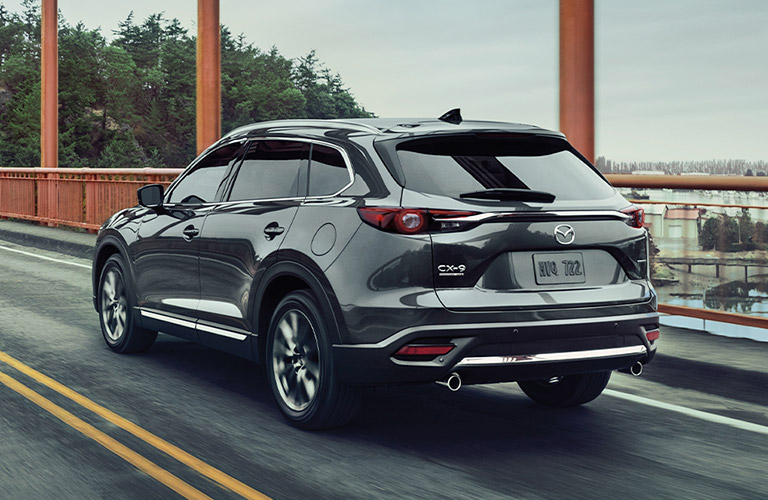 The rear and side image of a 2020 Mazda CX-9 driving down a highway.