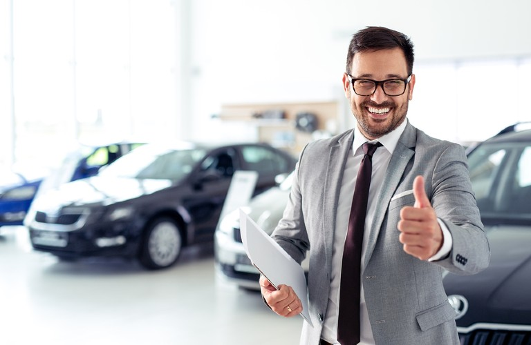 A man in glasses smiling with his thumbs up inside a car dealership.