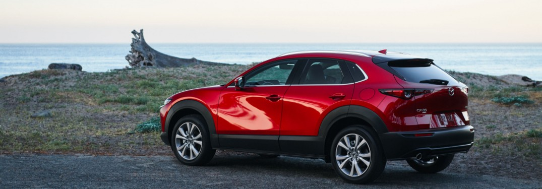 The side image of a red 2021 Mazda CX-30 2.5 S parked near the coast.