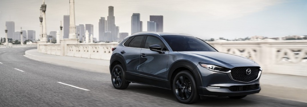 The front and side view of a gray 2021 Mazda CX-30 3.5 Turbo driving away from a city skyline.
