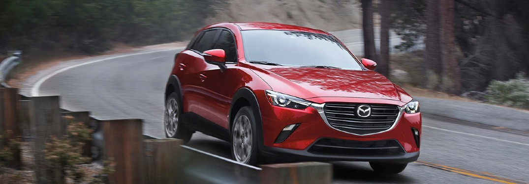 The front view of a red 2021 Mazda CX-3 driving down an empty roadway.