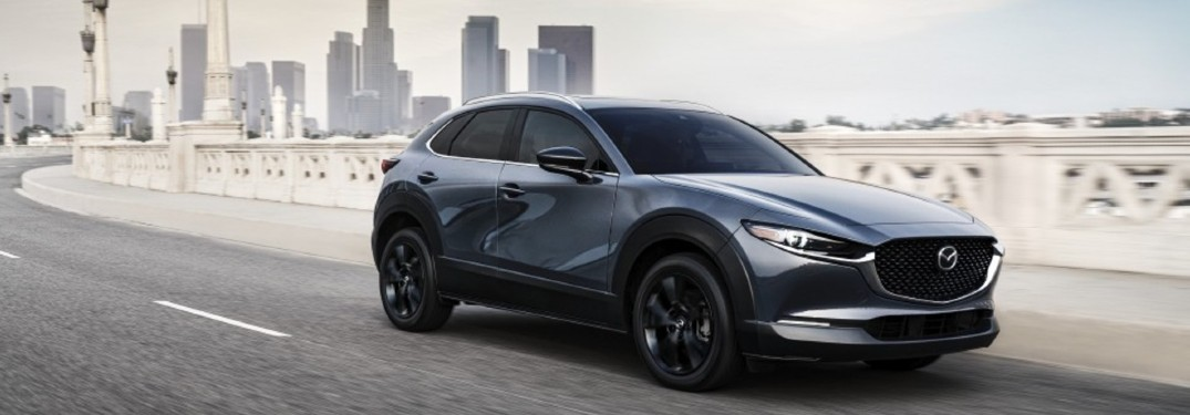 The front and side view of a gray 2021 Mazda CX-30 driving away rom a city.
