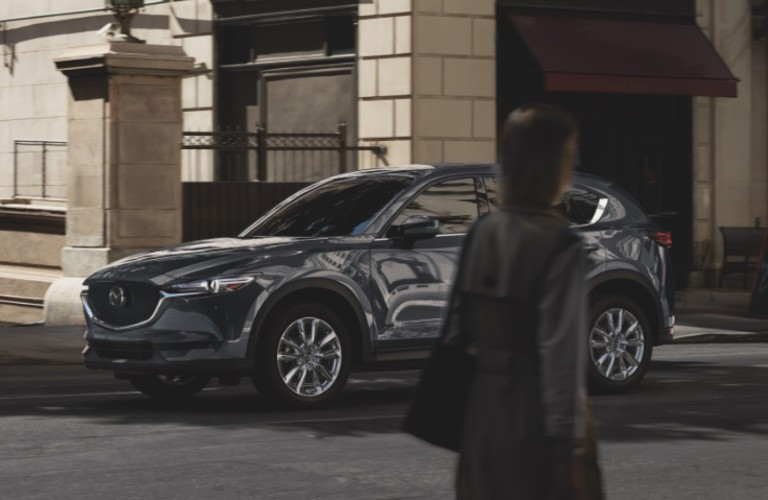 A paerson walking in front of a gray 2021 Mazda CX-5.