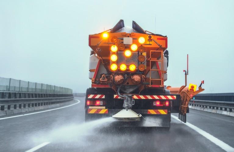 The rear view of an orange maintenance truck spreading salt on a Pennsylvania road.