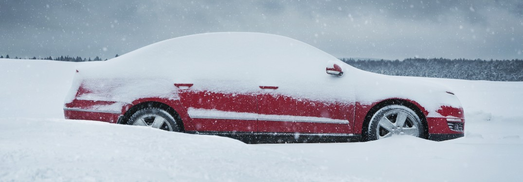 A red car parked in an open area with snow on top of it.