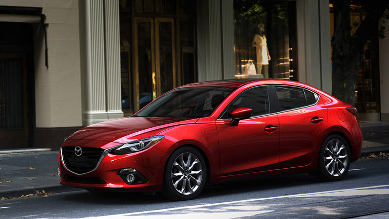 The side view of a red 2015 Mazda3 parked in a city.