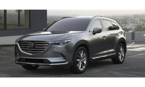 2019 Mazda CX-9 exterior shot with gray metallic paint job parked in front of a house with a foggy california town in the background