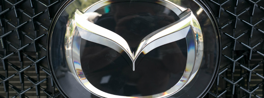close up of a Mazda logo embedded on a mesh grille