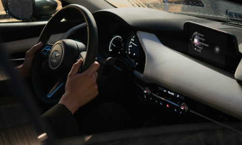 Person with hands on wheel of 2019 Mazda3 sedan