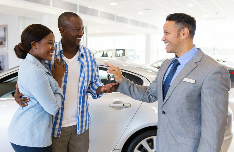 A man and woman accepting a key from a car salesperson