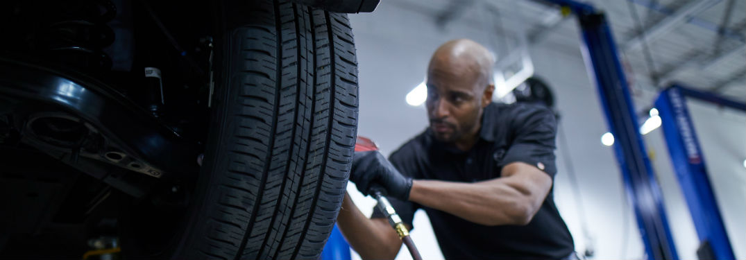 Mazda service technician using tool on tire