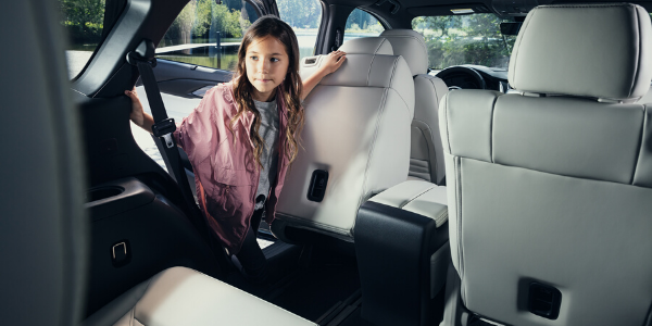 Young girl accessing the third-row seats of the 2020 Mazda CX-9 with second-row seat sliding forward