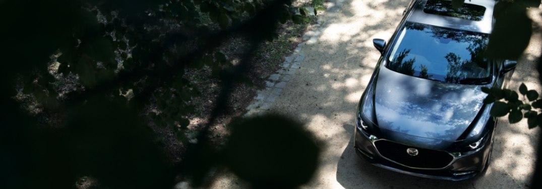 2021 Mazda3 Sedan driving down a rural trail