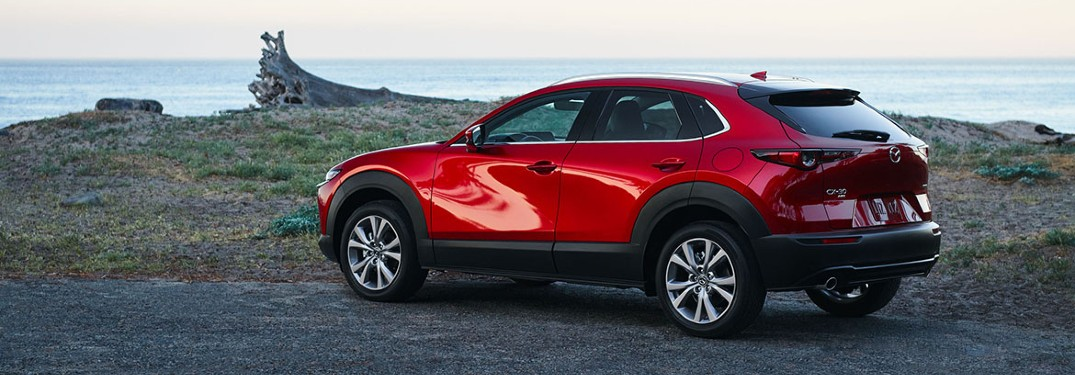 2021 Mazda CX-30 red parked by lake and grass hill