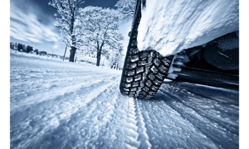 close up of car wheel in snow with motion blur and tracks