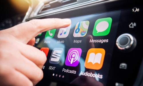 finger about to touch apple carplay display on car screen
