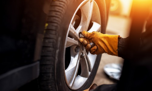 gloved hands putting lug nuts on car wheel with light flare