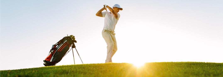 man driving a ball down a golf course