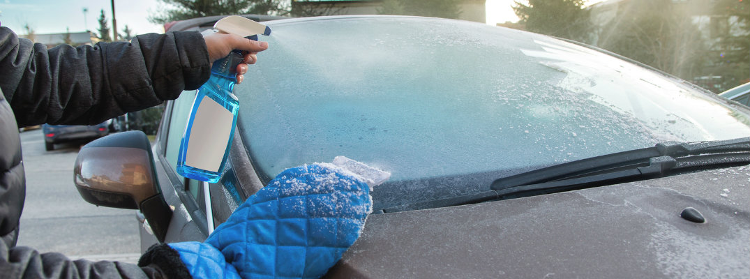 Two hands holding a scraper and bottle of defrosting fluid used to clear off windshield
