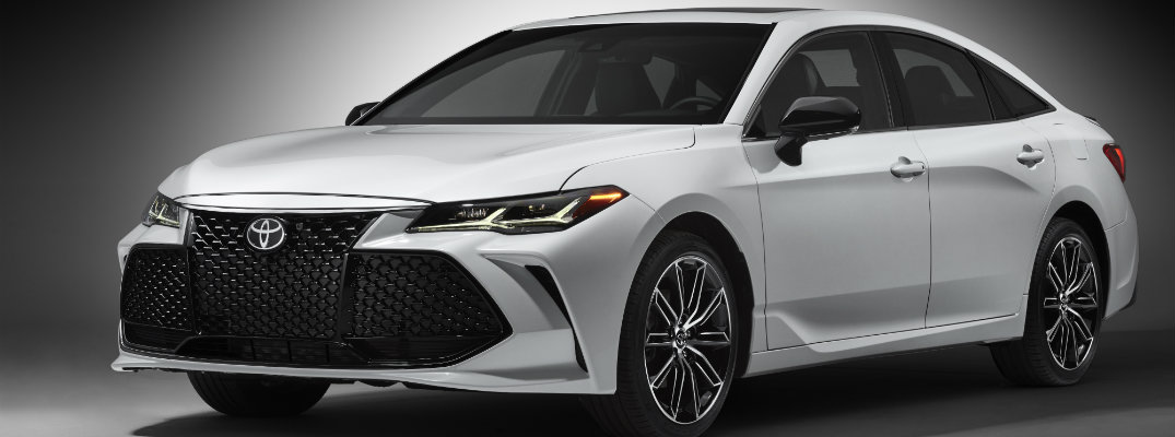 Long shot of white 2019 Toyota Avalon on silver background